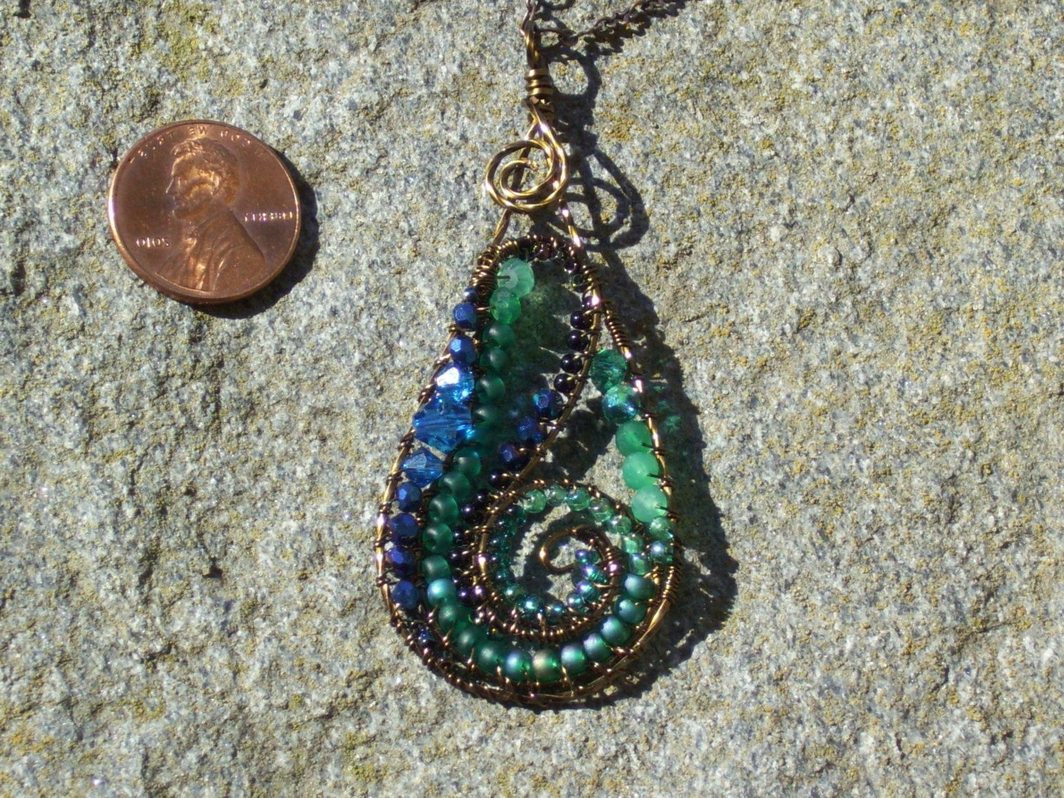 2018 Ponytail Wrapped In Copper Wire And Beads Regarding Bronze Green Blue And Black Swirl Medallion Necklace With Crystals (View 1 of 15)