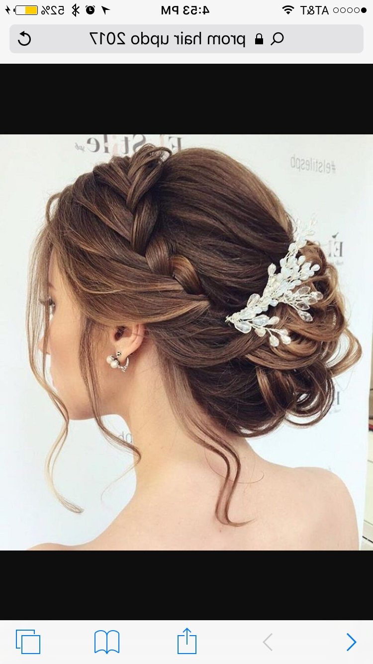 Cute Braid Flowing Into A Low Bun With A Few Strand Of Hair Hanging Intended For Fashionable Long Braided Flowing Hairstyles (View 9 of 15)