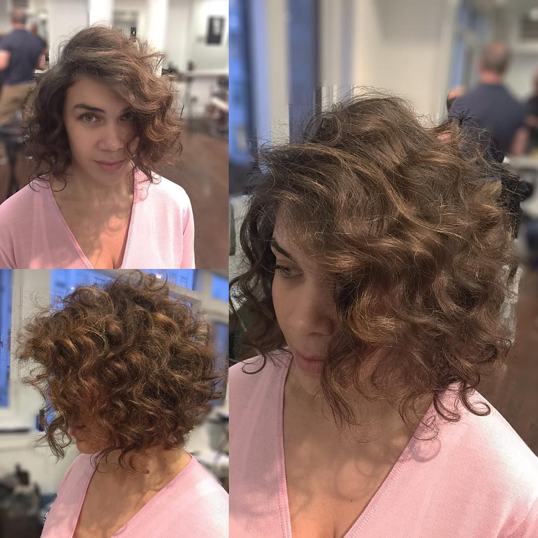 This Brunette Angled Bob With Large Soft Curls And Side Part Is A Pertaining To Angled Brunette Bob Hairstyles With Messy Curls (View 18 of 20)