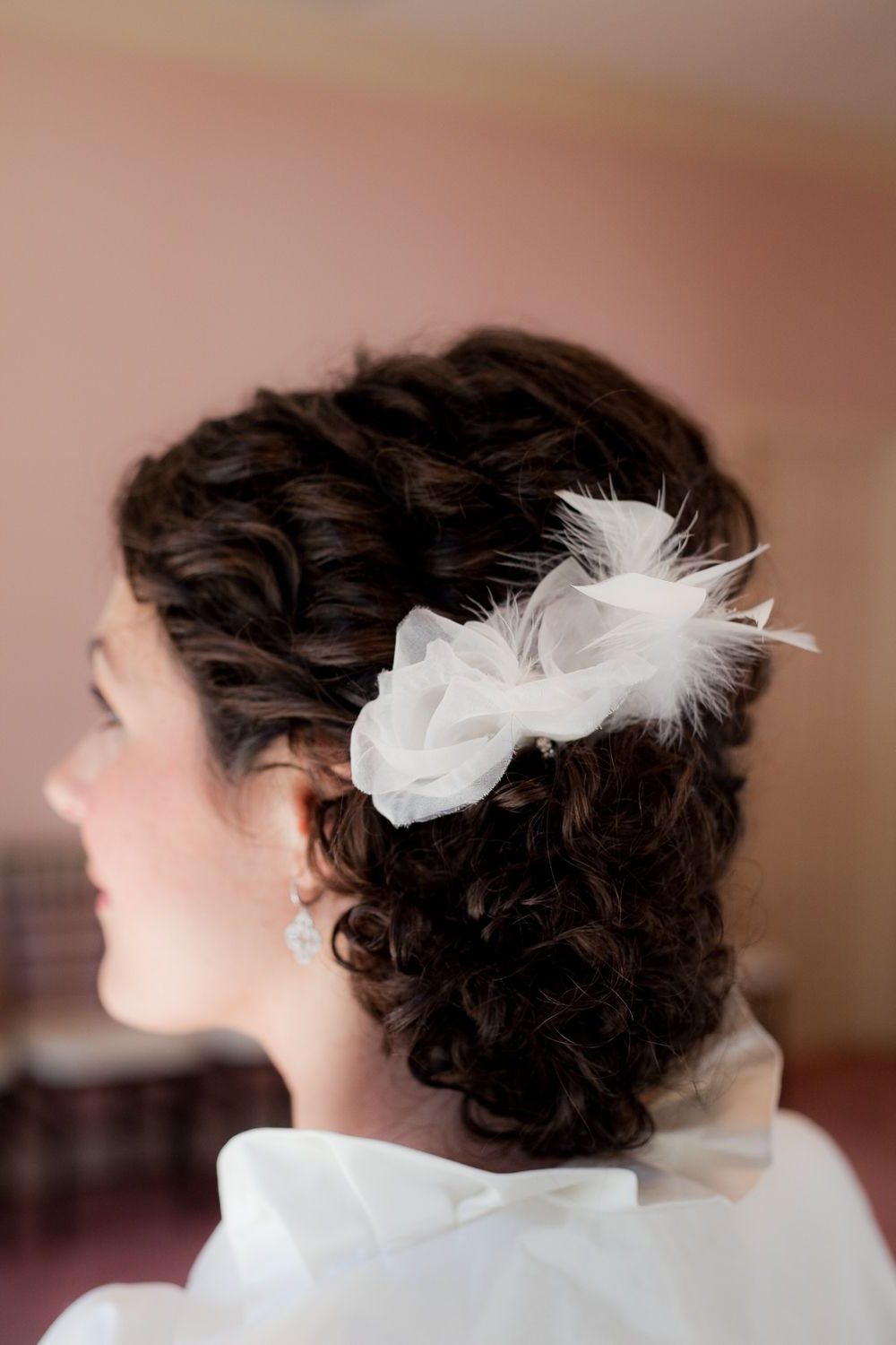 Current Wavy Low Bun Bridal Hairstyles With Hair Accessory Regarding Brunette Bride Wears Low Bridal Updo With White Flower Hair (View 4 of 20)
