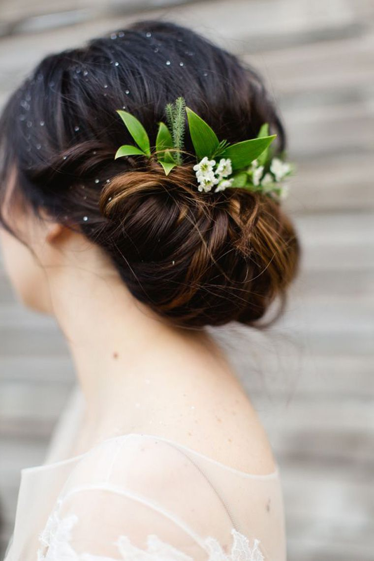 Low Tied Bun With Greenery As Hair Piece. Brides With Buns Via Throughout Current Low Petal Like Bun Prom Hairstyles (Gallery 6 of 20)