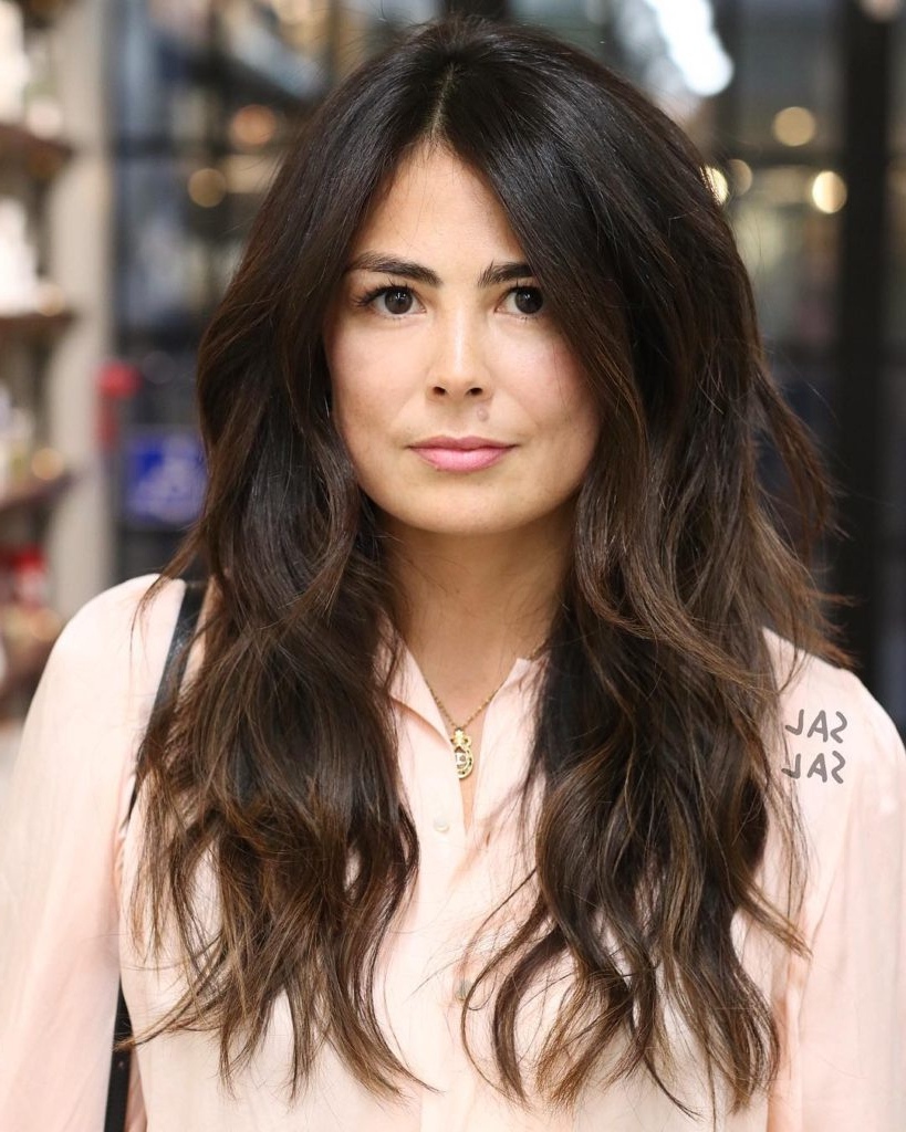 Women's Long Parted Layered Cut With Voluminous Bohemian Waves And Intended For Popular Voluminous Layers Under Bangs Hairstyles (Gallery 8 of 20)