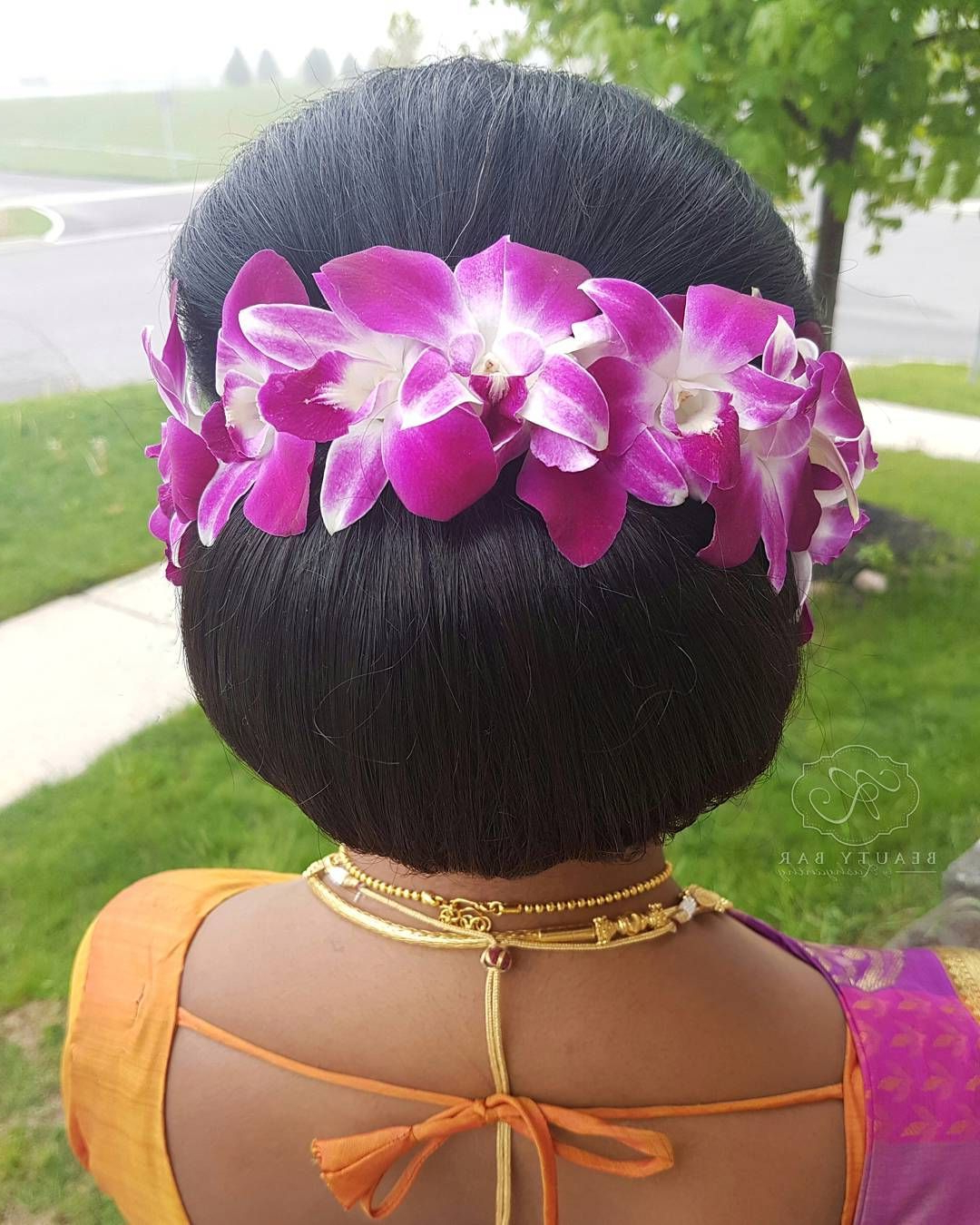 Best And Newest Floral Bun Updo Hairstyles Within Beautiful Fresh Orchid Flowers On A Classic Low Bun Updo (View 6 of 20)