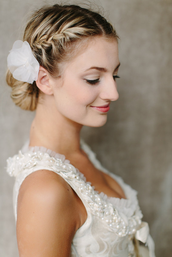 Romantic Low Braided Bun Updo With Silk Flower Regarding Well Known Reverse Braided Buns Hairstyles (View 8 of 20)
